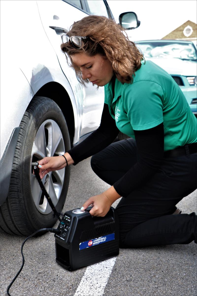 UNT Transportation Services staff member puts air in a tire.