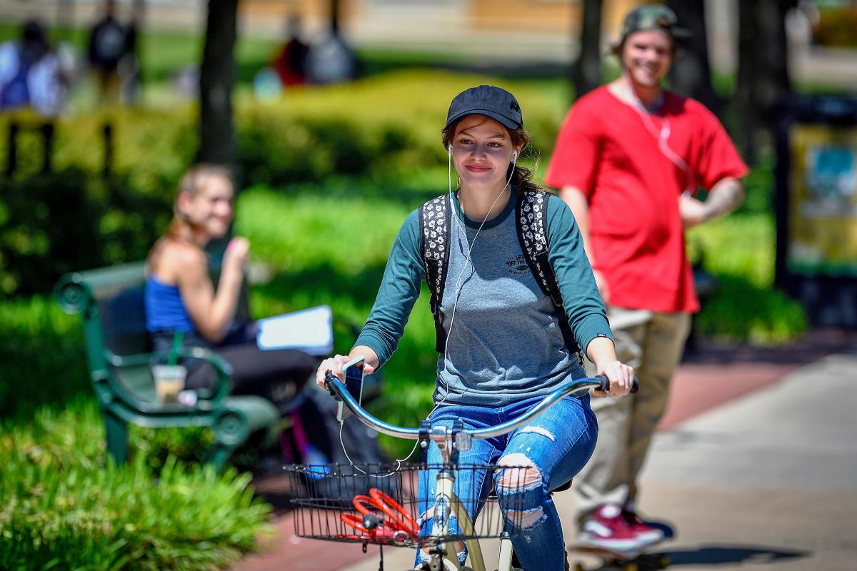 UNT community member riding a bike on campus